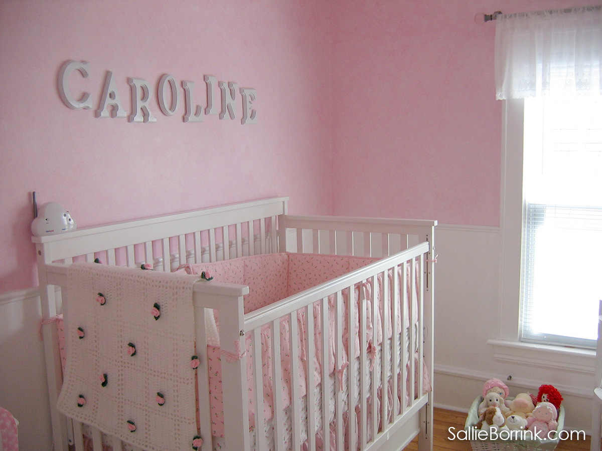 White baby bed with drawers in baby room with pink walls