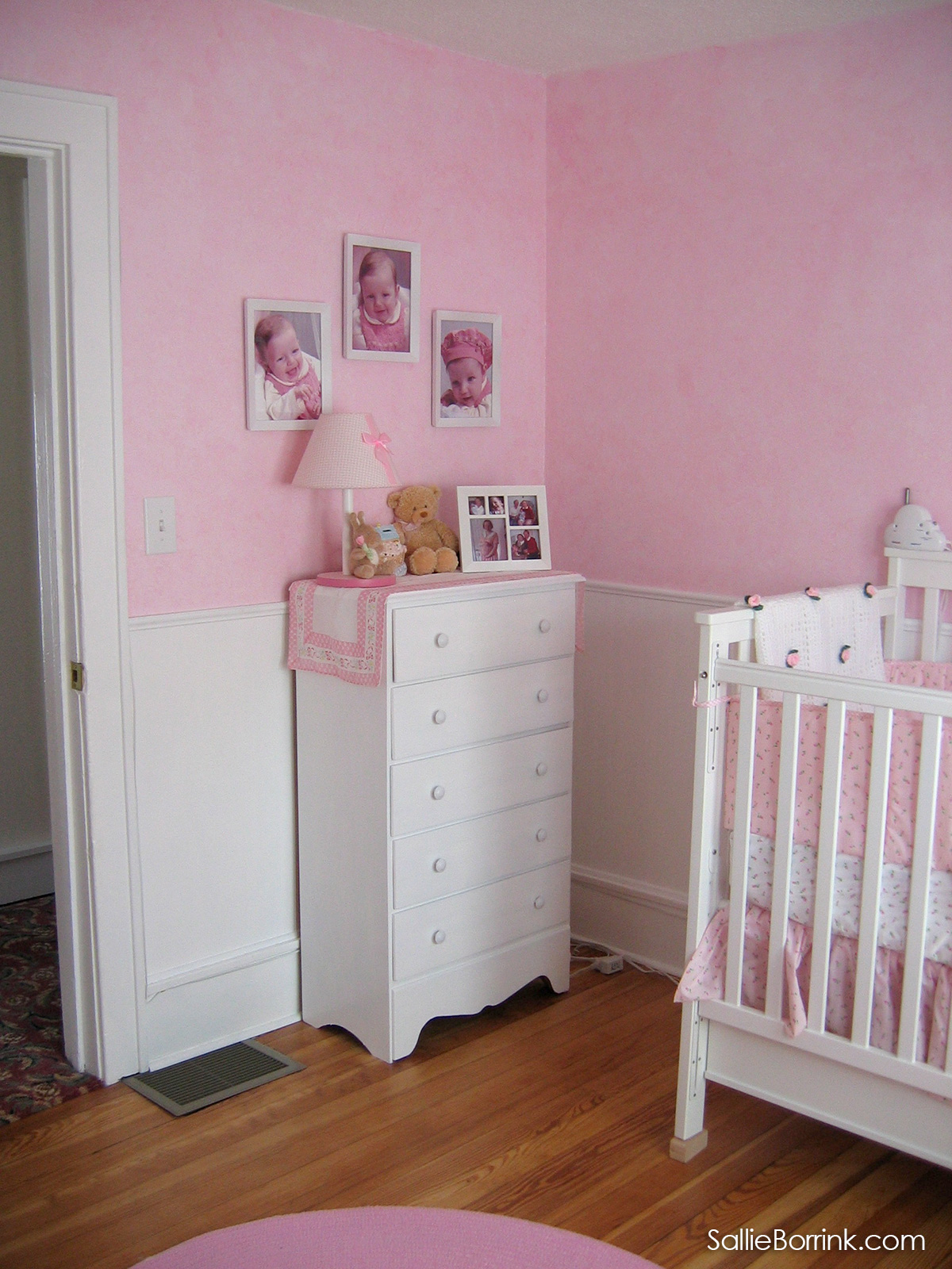 White dresser in baby nursery with pink walls, beadboard, chair rail, white baby bed, pink rug and wood floors