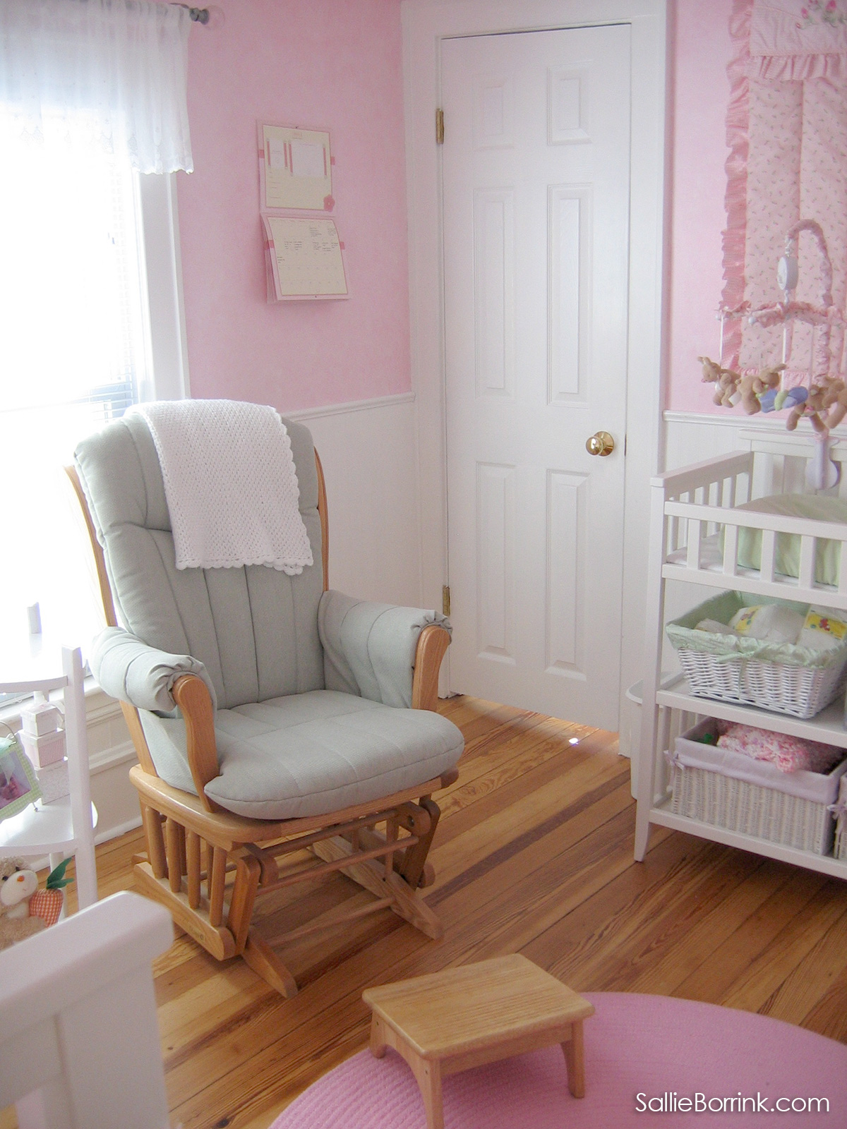 Glider chair with light green cushions in pink baby room with white woodwork, white changing table, and white bed.