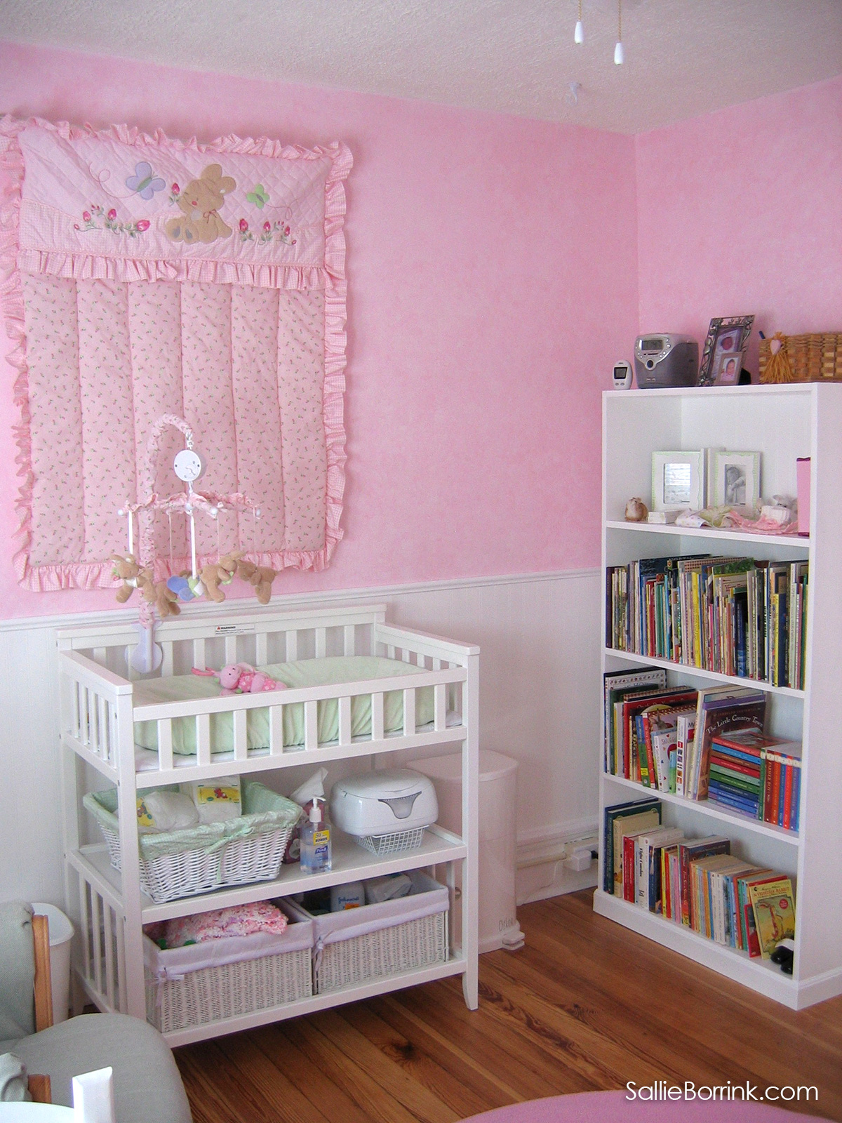 White changing table and bookcase in pink baby nursery