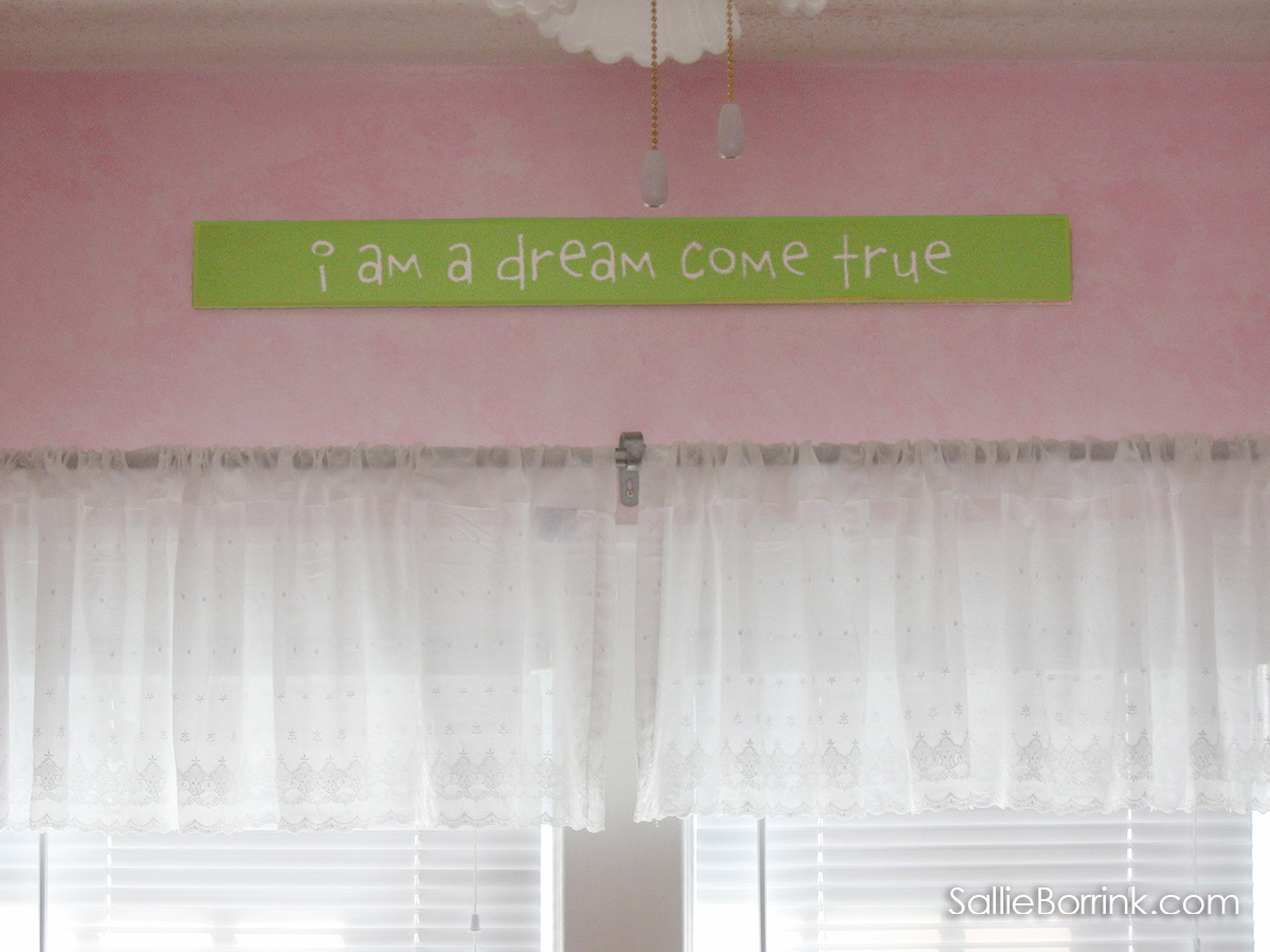 I am a dream come true green sign above white valence curtains in pink baby nursery